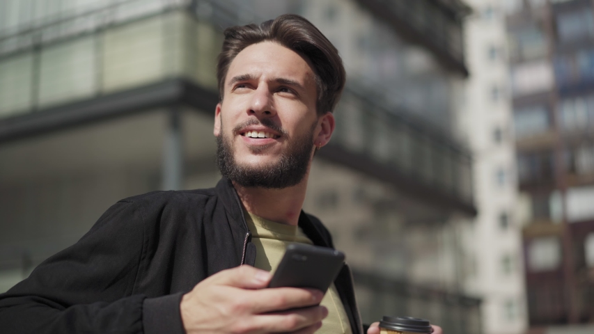 Camera approaching handsome young man typing messages on cell phone leaning on railing in street. Man looking away and thinking, takeaway coffee cup in his hand | Shutterstock HD Video #1033870394