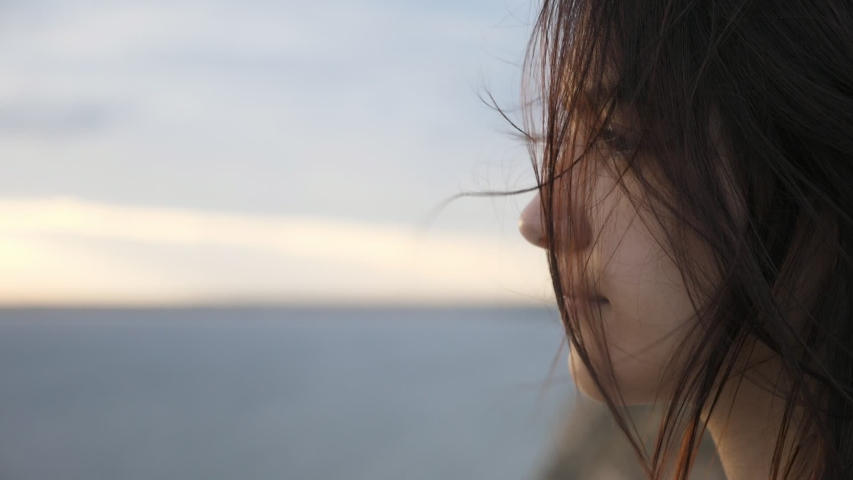 Wonderful closeup of magnetic brunette girl with long hair standing on a sea beach and thinking at the shining sea at cloudy sunset in summer in slo-mo