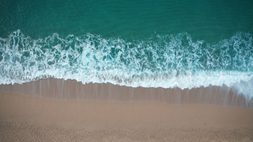 Drone view of beautiful seamless never ending footage while turquiose sea waves breaking on sandy coastline. Aerial shot of golden beach meeting deep blue ocean water and foamy waves Royalty-Free Stock Footage #1033900535