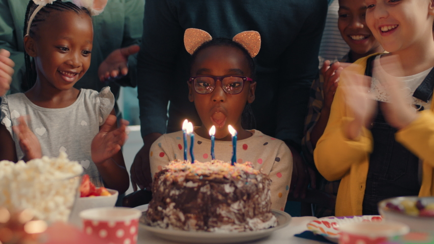African american birthday girl blowing candles on cake making wish celebrating party with friends children having fun celebration at home 4k footage