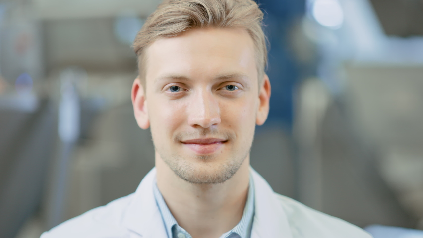 Close Up of a Handsome Young Blond Male Portrait Shot. He's a Professional Employee. Man Looks and Smiles at Camera. Expresses Success and Happiness. He Has Blue Eyes and Light Beard.   Shutterstock HD Video #1033924541