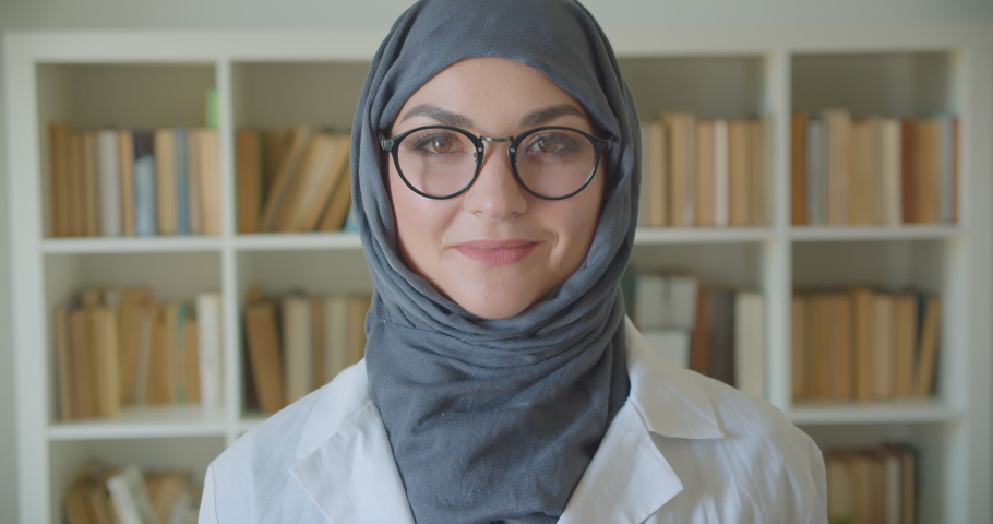 Closeup portrait of young muslim attractive female doctor in hijab and glasses looking at camera smiling happily standing in the library indoors Royalty-Free Stock Footage #1033938743