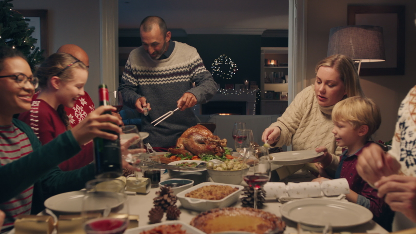Family christmas dinner man cutting turkey serving delicious meal at festive celebration people sitting at table enjoying delicious feast celebrating holiday at home 4k footage | Shutterstock HD Video #1033939868