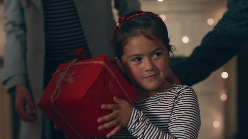 happy little girl excited to open present on christmas shaking gift box curious child enjoying festive holiday celebration with family at home 4k #1033940546
