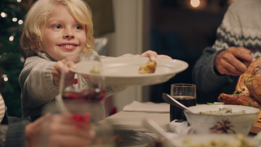 Cute little boy enjoying christmas eve dinner with family eating delicious homemade meal passing plate sharing holiday feast at home 4k footage | Shutterstock HD Video #1033940591