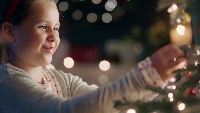 Happy little girl decorating christmas tree with beautiful ornaments and baubles enjoying festive decorations at home on calm winter evening 4k footage