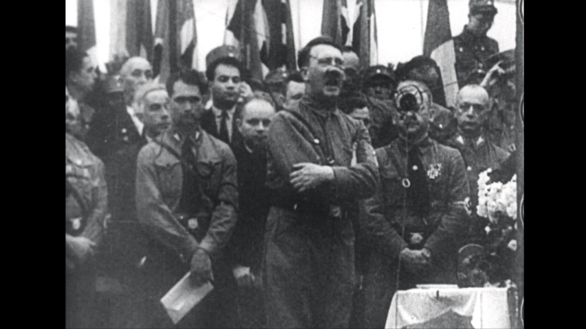 1950s: Adolph Hitler speaking into microphone.