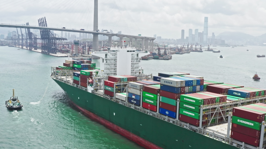 Hong Kong, Hong Kong - Jul 8, 2019: Cargo ship transporting shipment container arriving Hong Kong port, drone aerial view. Freight transportation, import export business or industrial concept
