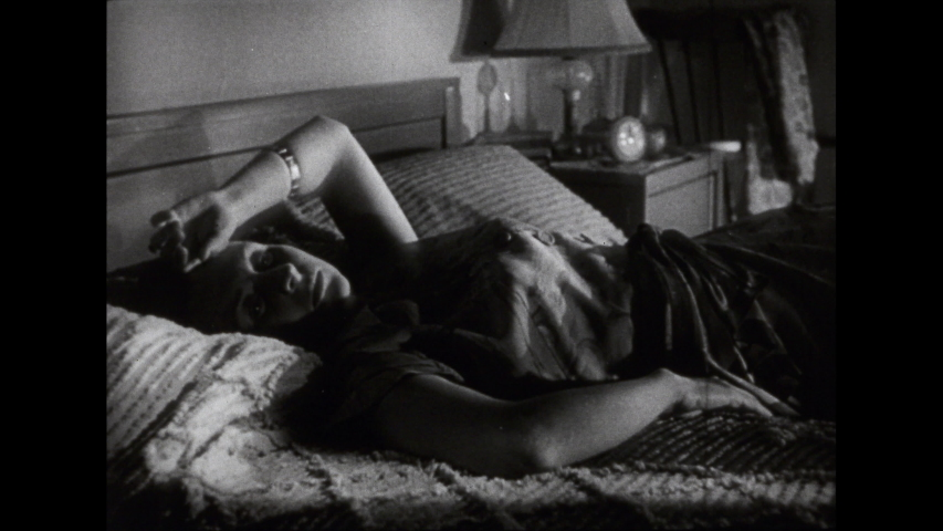 1950s: Zoom out on woman lying in bed. | Shutterstock HD Video #1033953497