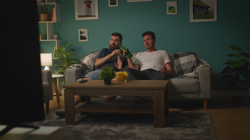 Two young men talking and getting upset while watching sport game on TV at home | Shutterstock HD Video #1033982030