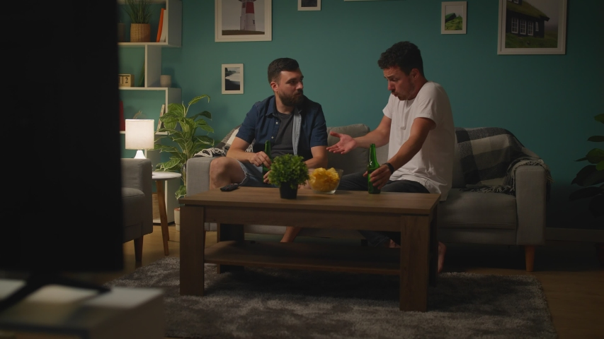 Two young men are watching game on TV and anger discussing game and losing team | Shutterstock HD Video #1033982036