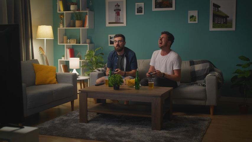 In Living Room Two Brothers Sitting on a Couch Playing Video Game | Shutterstock HD Video #1033982117