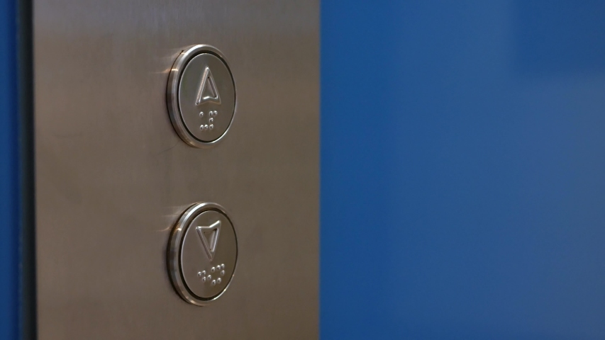 Female Hand Pushing Elevator Button in Office Center or Hotel. Young Woman Pressing Lift Button Up. The finger presses the button with the arrow pointed up. Closeup. 4K
