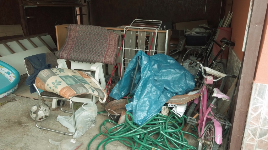 Panning across cluttered storage room in messy garage   Shutterstock HD Video #1033982678