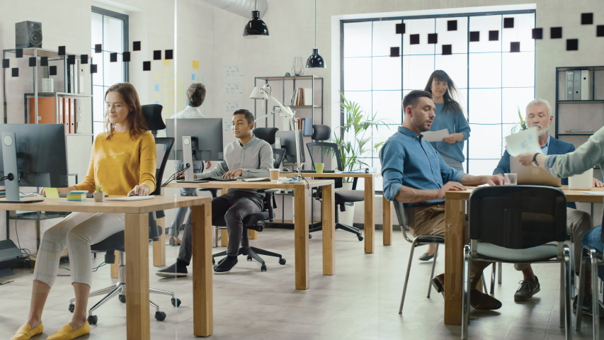 In the Stylish Open Space Office: Diverse Group of Enthusiastic Business Marketing Professionals Use Computers, Have Meetings, Discussing Project Ideas, Brainstorming Startup Company Strategy | Shutterstock HD Video #1033983044