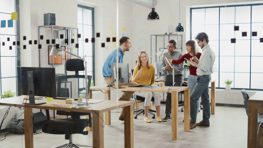 In the Stylish Office: Diverse Group of Business Colleagues Have Meeting. Multi Ethnic Team of Businesspeople Use Desktop Computer, Chat and Watch Videos, Discuss Startup Statistical Growth Strategy