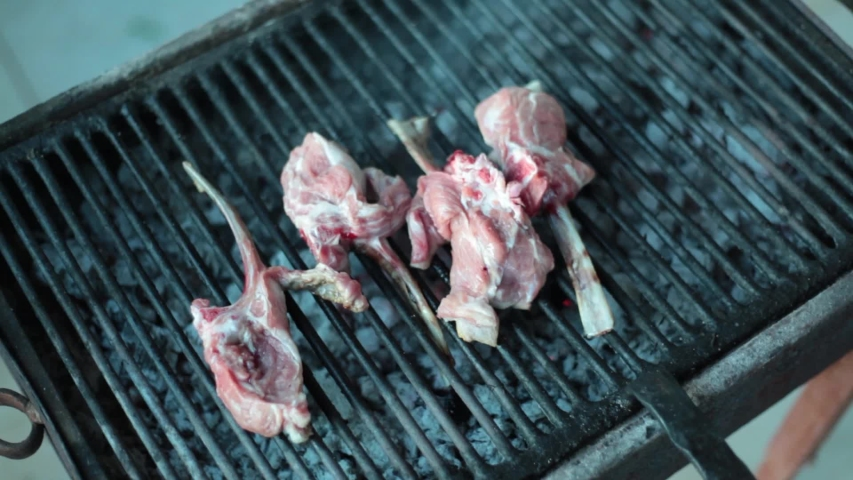 Fresh meat of lamb on ribs, cooked on the grill, with a smoke, for cooking, called the rack of lamb on the grill. Gourmet food concept | Shutterstock HD Video #1033991303