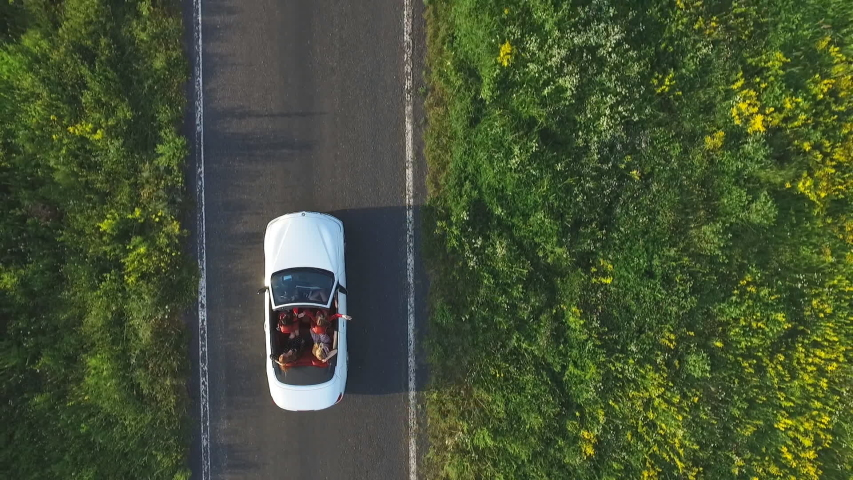 Aerial shot of white convertible car riding through empty rural road. Four young unrecognizable women travelling at cabriolet. Flying over auto driving at countryside road on summer day. Slow motion | Shutterstock HD Video #1034000951