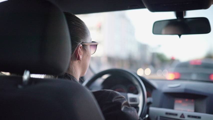 Driver waiting in red lights during traffic jam and rush hour in busy street. Woman sitting in car. Commuter in traffic jam. Travel, commute and transport. Inside back view of vehicle.