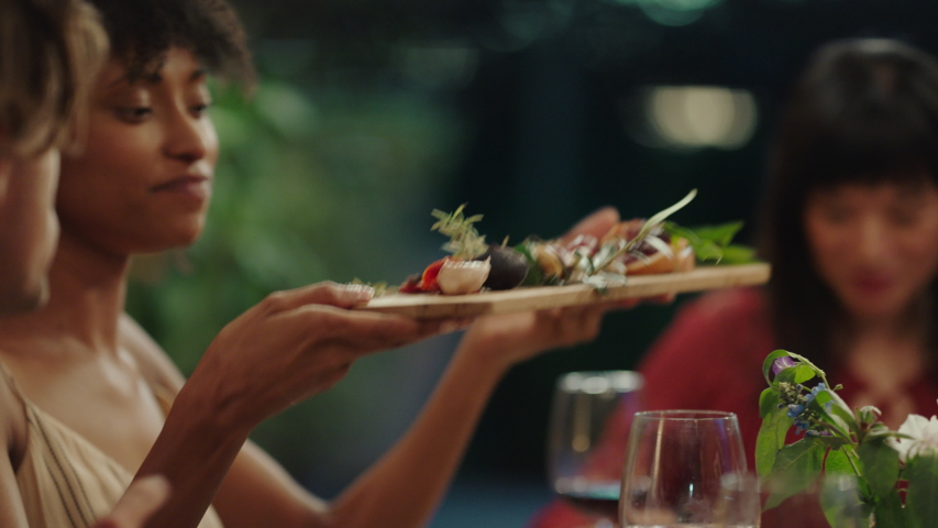 Happy friends celebrating at dinner party eating mediterranean food sharing platter sitting at table enjoying evening feast 4k footage | Shutterstock HD Video #1034004923