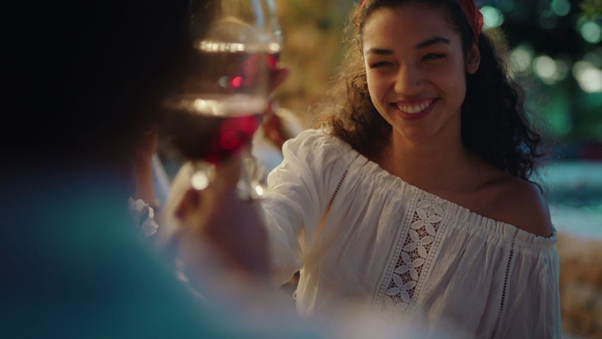Beautiful mixed race woman enjoying dinner date flirting with man couple drinking wine making toast celebrating travel in italy romantic evening together 4k