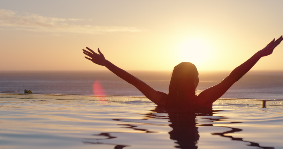 Woman relaxing in swimming pool at luxury hotel spa enjoying beautiful sunset view of ocean mediterranean travel holiday resort 4k