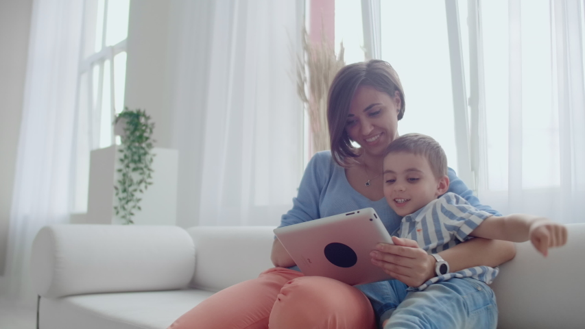 Mother And Son Using Tablet Looking At Screen And Talking On Sofa In Cozy House. #1034009939
