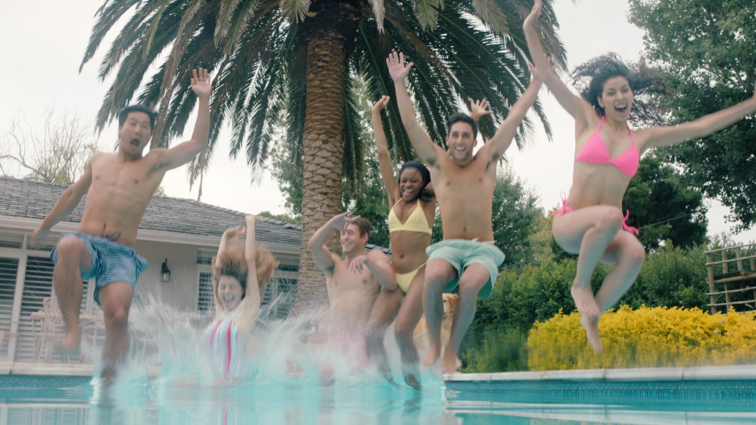 Cool friends jumping in swimming pool having fun celebrating summer vacation together group of teenagers enjoying pool party on sunny day underwater view 4k