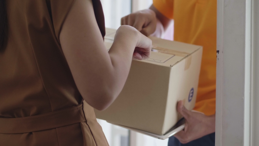 Young delivery Asian man holding a cardboard box while Asian young woman checking address on the box.