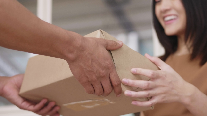 Close up hands Asian woman receive a cardboard box from a man's delivery holding at home. Royalty-Free Stock Footage #1034015099