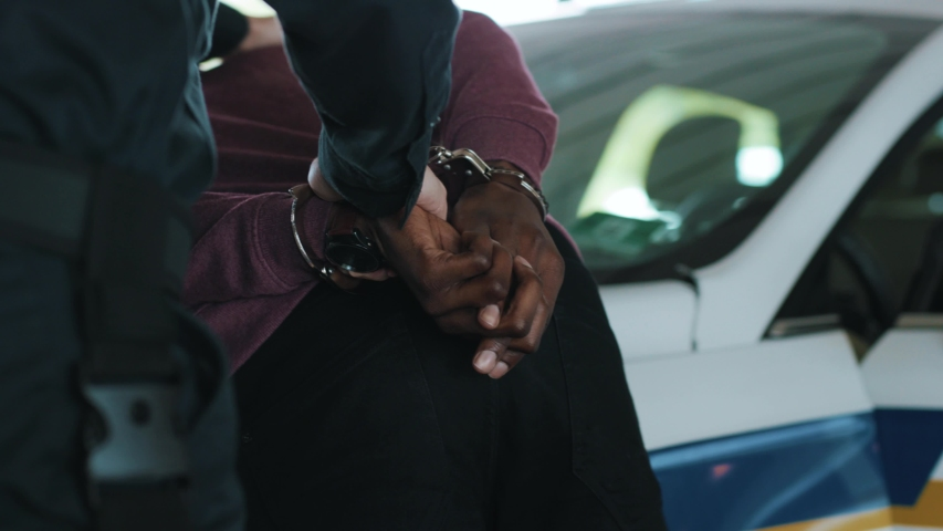 Close up hands policeman arrest robber in handcuffs standing near the car