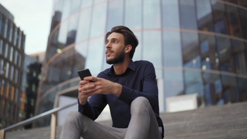 Camera approaching businessman sitting on steps of modern office building and text messaging on cell phone. Young man looking away dreamily
