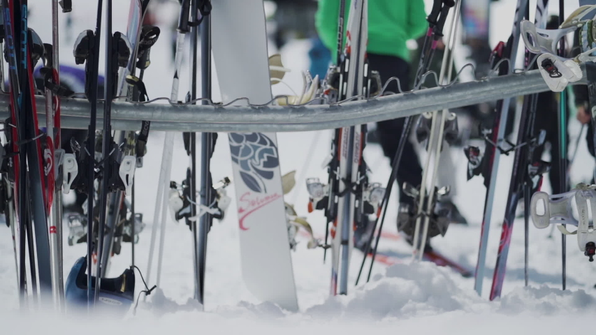 Yosemite, CA / United States - 03 29 2019: Slow motion shot of skis and snowboard on rack in snow. #1034018762