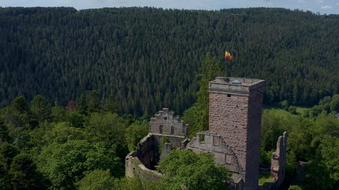 Aerial view of Zavelstein in Germany.  Camera rotates left around castle ruins, with Black Forest as the background. Panorama view.