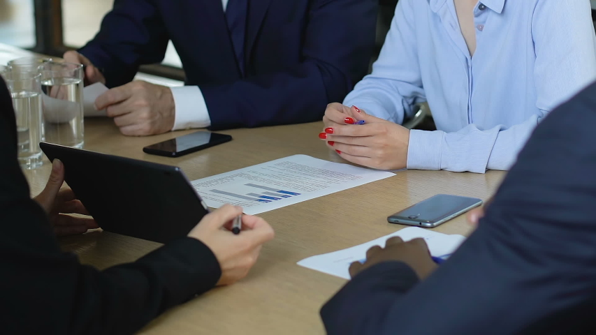Business partners discussing company budget, charts on table, success strategy #1034022035