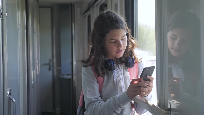 Teenager girl traveler with backpack stands by the window of the train car with a smartphone. travel transportation railroad concept. the girl in the train at the window corresponds the girl in the | Shutterstock HD Video #1034025863