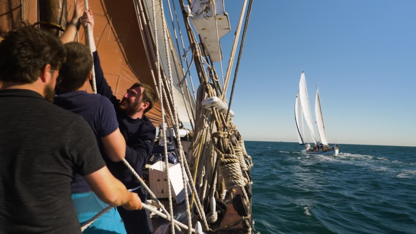 Antwerp, Antwerp / Belgium - 09 27 2018: Crew hoisting a sail on a sailing boat with a white ketch off the starboard bow, Antwerp, Belgium, September 27, 2018