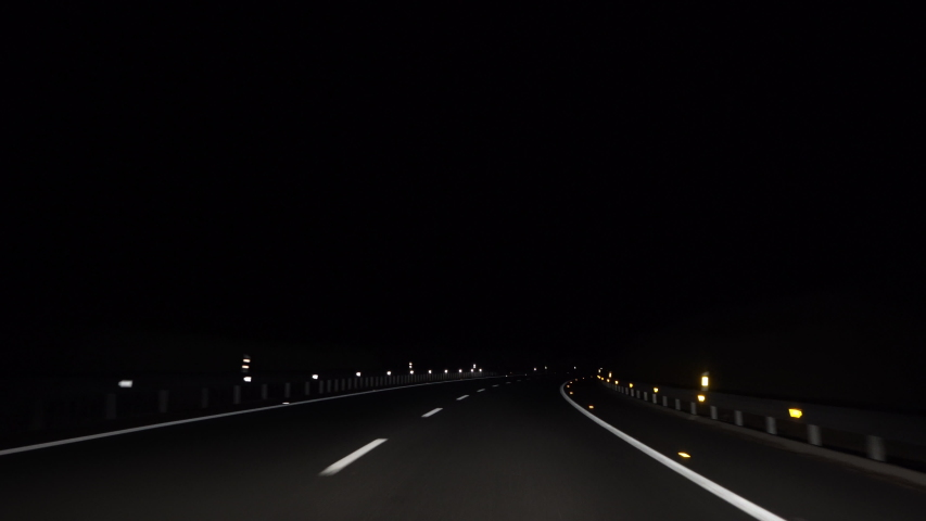 4K, POV view of car driving on road of highway at night in Spain. Drive on an empty road in the dark evening. A car drives on a freeway. Asphalt with white line at new road.