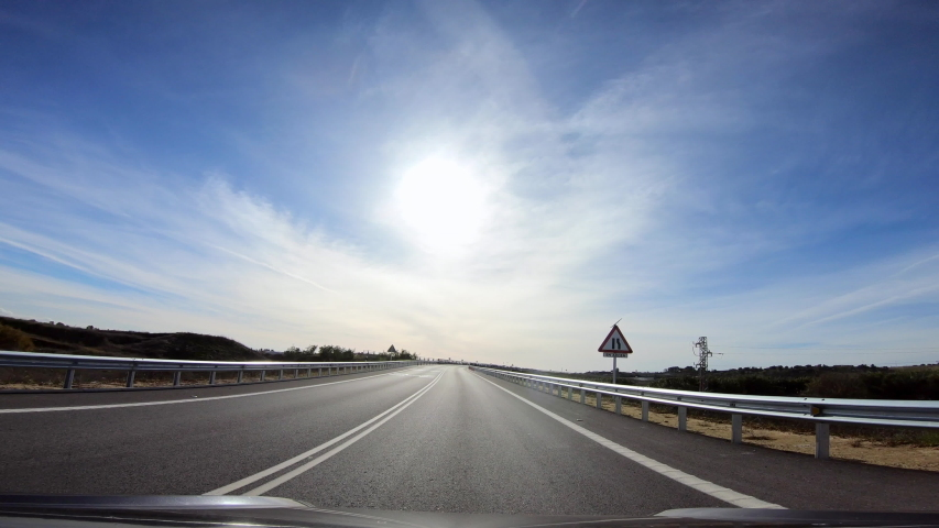 4K, POV view of car driving on highway in the provinces of Seville, southern Spain. A car drives on a freeway. Asphalt with white line at new road.