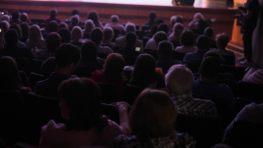 Full auditorium of people. Spectators watch performance show or view in theater, back view. Staging in theatre. Many people in playhouse sitting in chairs and looking at scene. | Shutterstock HD Video #1034031548
