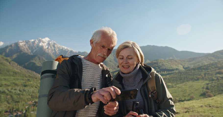 Old couple having a hike in spring mountains, then stopping to take a picture on a smartphone. Senior caucasian family spending time together travelling after retirement - tourism concept 4k | Shutterstock HD Video #1034041928