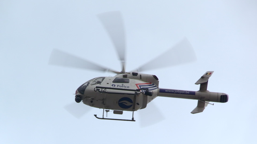 Brussels, Belgium - 03 31 2019: a beautiful close up and overhead view of a police helicopter keeping surveillance during a demonstration, SLO-MO