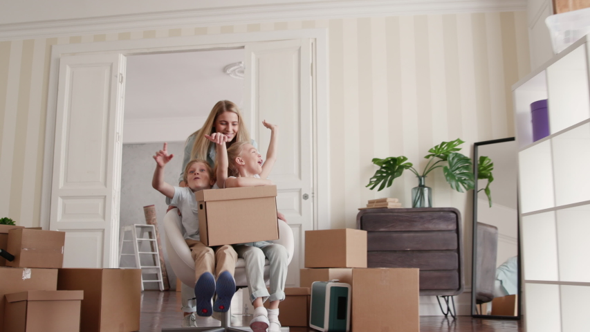 Family Group Move in Beautiful Flat in Modern Building. Two Babies Ride a Chair Inside Big Real Estate. Carton Packaging of Caucasian Small Child. Funny Adult Mom on Relocating Day or Active Unpacking