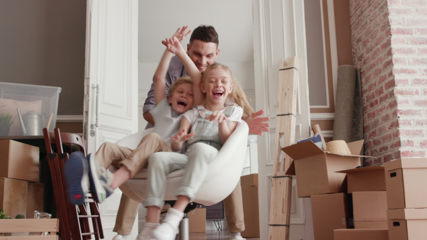 Active Family Group Move in Rent Real Estate. Positive Looking at Relocating or Unpacking of Carton Pack by Playful Dad. Two Caucasian Babies Ride a Chair. Enjoying Life or Dream of Small Child by Day
