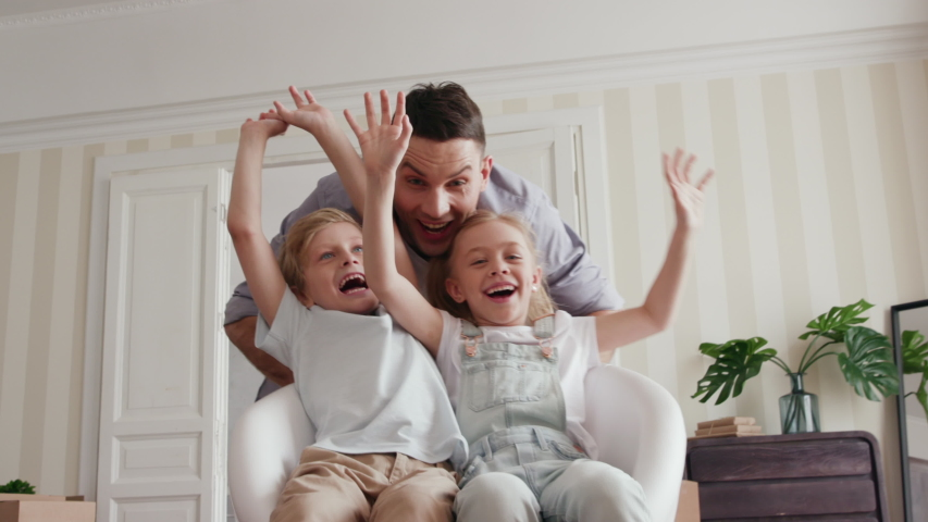 Family Group Moves in Big Rent Real Estate. Son and Small Daughter Relocate or Ride a Chair. Positive Mood of Looking at Casual Unpacking of Carton Pack. Funny Face of Playful Dad or Beautiful Child #1034046743