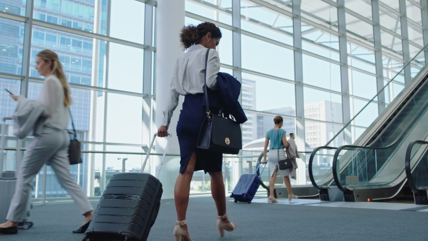 business woman traveler walking in airport with trolly bag going up escalator female executive traveling international for business trip checking messages on smartphone 4k