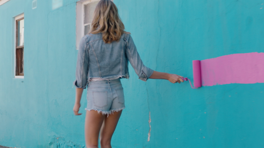 Graffiti girl artist woman painting wall with pink paint walking in city street confident rebellious female enjoying artistic expression with urban graffiti art   Shutterstock HD Video #1034049203