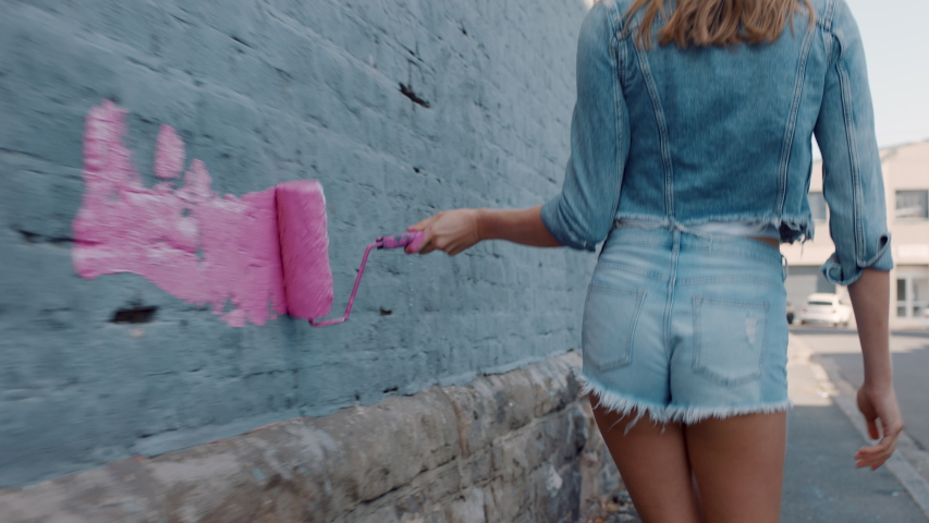Graffiti girl artist woman painting wall with pink paint walking in city street confident rebellious female enjoying artistic expression with urban graffiti art | Shutterstock HD Video #1034049206