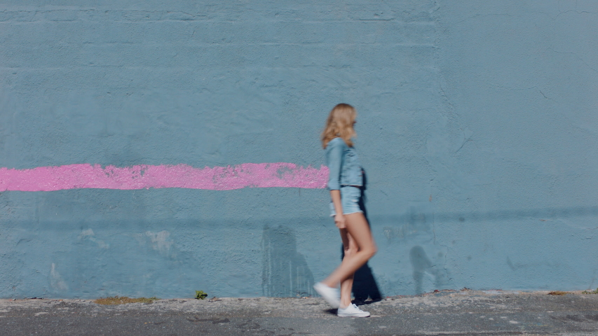 Graffiti girl artist woman painting wall with pink paint walking in city street confident rebellious female enjoying artistic expression with urban graffiti art Royalty-Free Stock Footage #1034049209