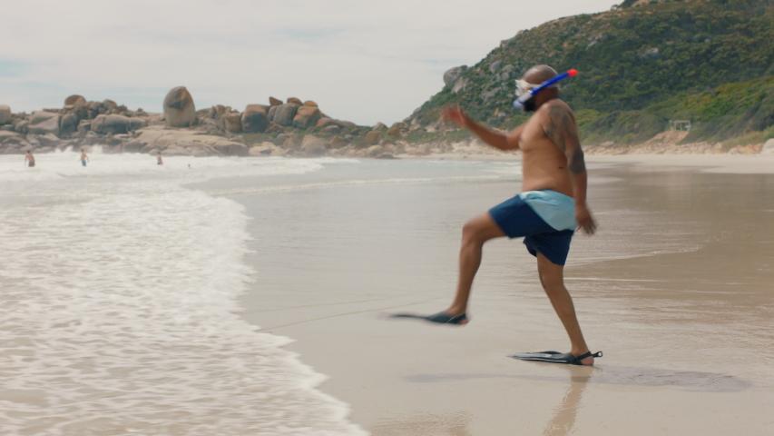 Funny african american man walking on beach in sea water wearing flippers getting ready to swim enjoying summer by ocean 4k